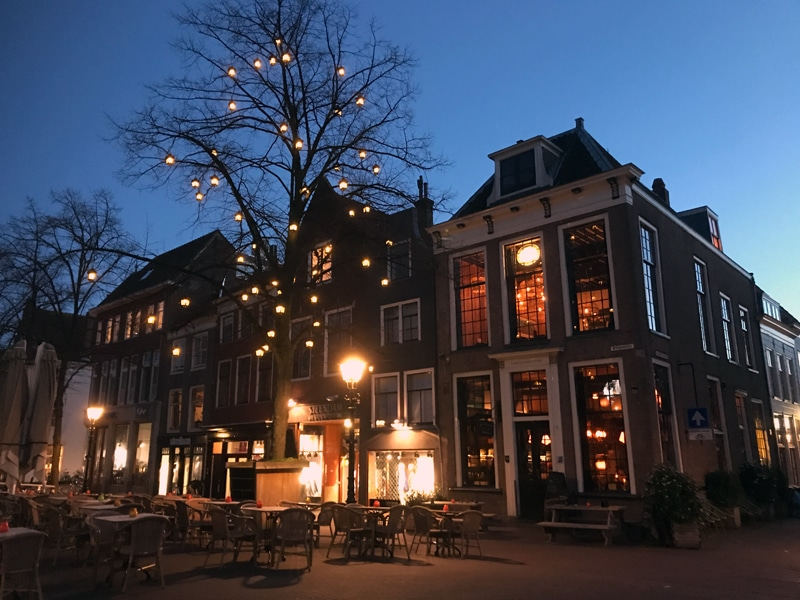 Delft by night with outside terrace in front of a local cafe.