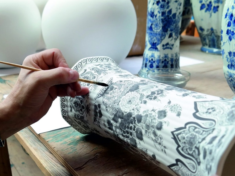 Royal Delft Experience. A worker is painting a vase.