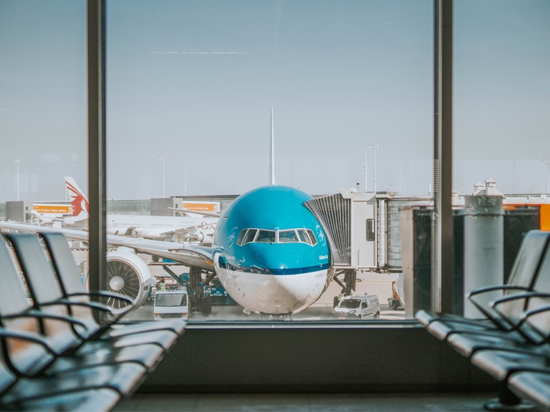 KLM airplane waiting at the gate. View from the terminal.